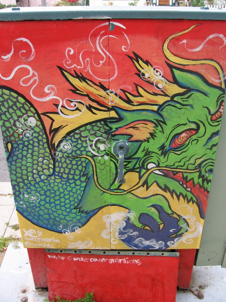 One side of a fun utility box has been boldly painted with a fiery green dragon.