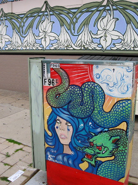 A lady and another scaly dragon on the opposite side of the box. A floral mural decorates a nearby store's wall.