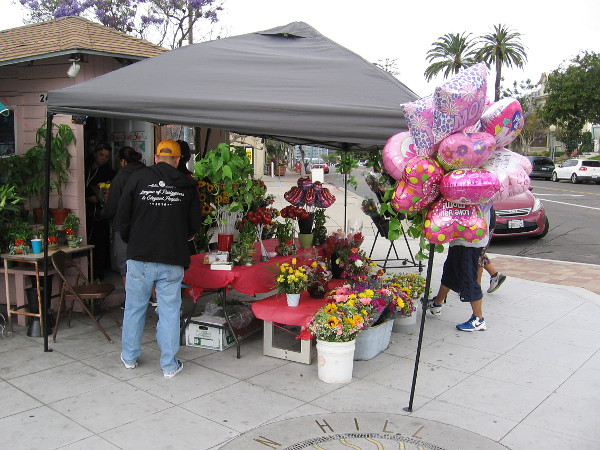 Lots of balloons and flowers for sale at the corner of Broadway and 25th Street. It's Mother's Day.