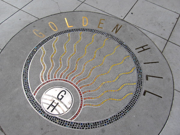 A beautiful bit of shining art inlaid in the sidewalk. A marker at the top of Golden Hill.