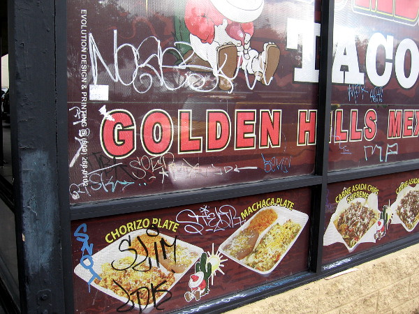 A Mexican taco shop and graffiti on the windows. The neighborhood today is a bit rundown, but sunny and pleasant.