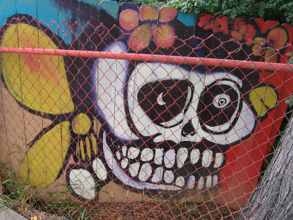 A wooden fence along the sidewalk contains amazing, colorful murals, beginning with this flowery skull.