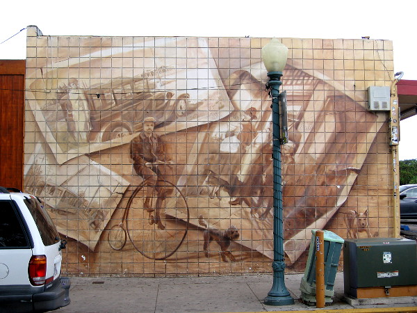 Sepia tone mural on Fern Street in South Park features man riding an old-fashioned penny-farthing and nostalgic images from San Diego's past.