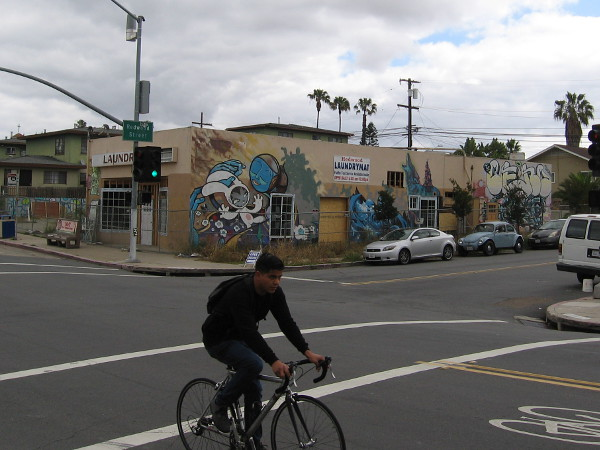 Bicyclist rides south down 30th Street in North Park, past an old closed laundromat at Redwood Street. This building's walls have long featured diverse and changing works of street art.
