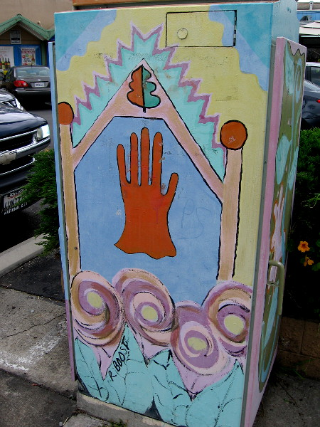 Another side of the same utility box. A hand stands treelike at the center of the unusual metal canvas.