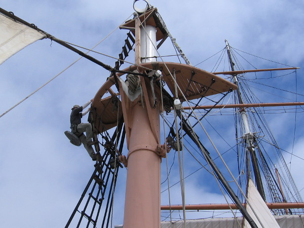Climbing carefully up to the very top of the foremast to apply a protective cap, to prevent exposed iron from rusting, decaying.