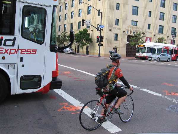 Morning commuter on a bicycle waits alongside a bus for a traffic light on Broadway.