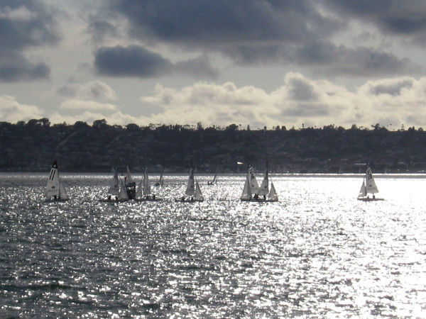 Small sailboats float on a sheet of silver, beneath dramatic clouds.