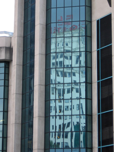 Reflection in glass panes of the Parking Palace shows the iconic sign atop the El Cortez.