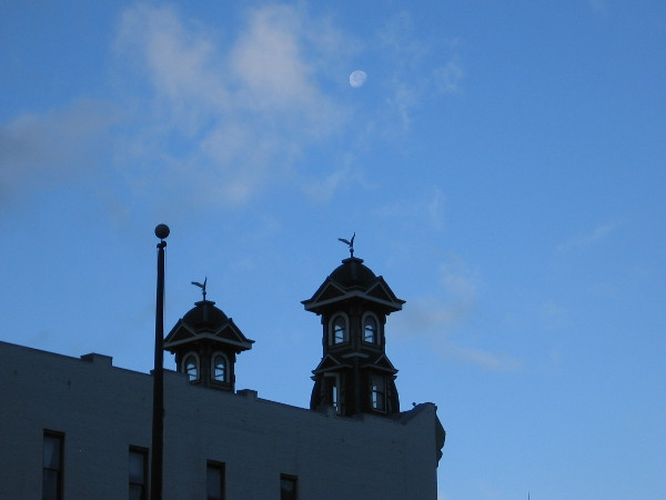 Photo of moon, high above towers of Louis Bank of Commerce Building's facade, one block over on Fifth Avenue. This famous location was home to Wyatt Earp's Oyster Bar gambling hall and saloon.