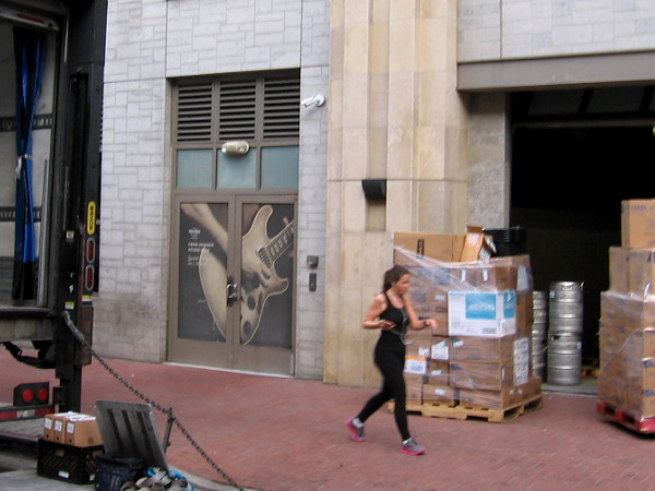 Morning deliveries and jogger near electric guitar on employee door of the Hard Rock Hotel.
