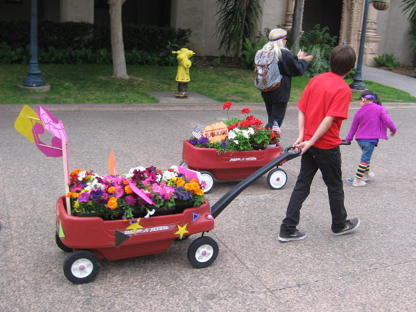 Towed by young people, floral displays head down Balboa Park's central El Prado.