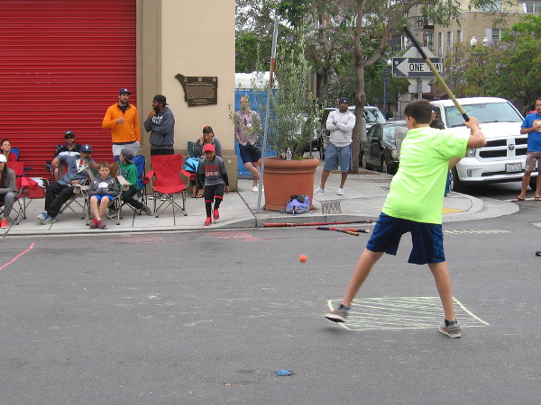 A teammate is ready to strike the bounced rubber ball with a taped wooden broom handle. Lots of people were watching on either side of Columbia Street.
