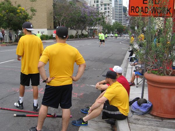 Members of the Street Rookies, in yellow shirts, watch as their offense tries to score more runs.