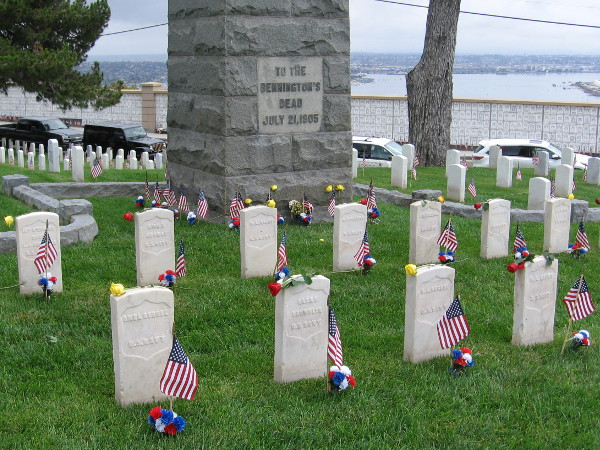 American flags at the grave markers around the USS Bennington Monument. The granite obelisk remembers those sailors who lost their lives when the warship's boiler exploded in San Diego Bay.