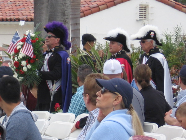 Ceremonial wreaths approach the rostrum. Many organizations presented wreaths, including the Knights of Columbus shown here.