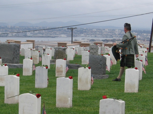 A bagpiper, after playing Lament for a Soldier, exits across the green grass, where the fallen lie eternally.