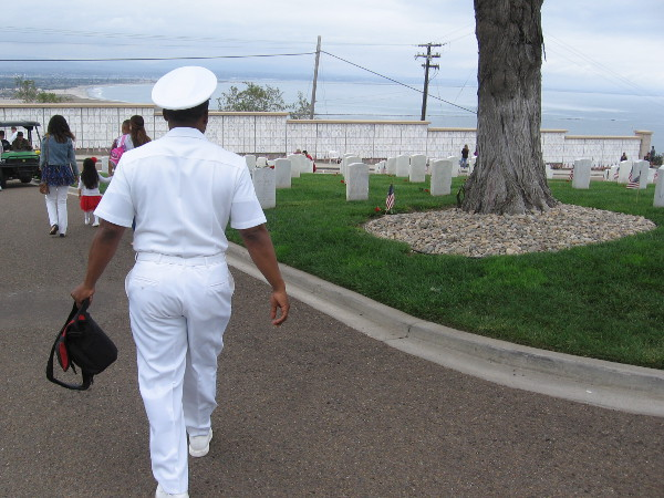 A Navy officer walks down a cemetery driveway, which overlooks the channel entrance to San Diego Bay.