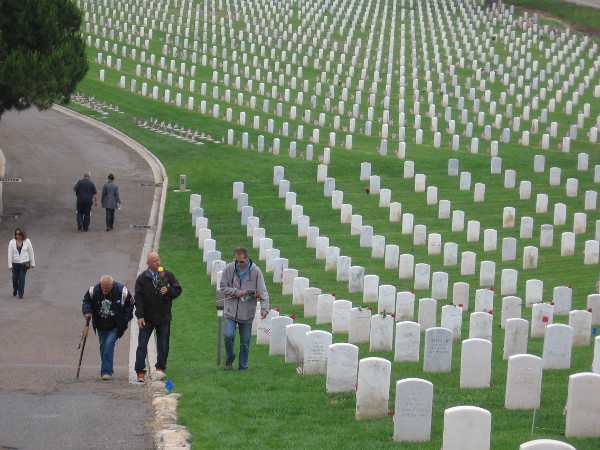 The living walk thoughtfully through Fort Rosecrans National Cemetery in San Diego.