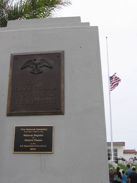 The main entrance plaque at Fort Rosecrans National Cemetery. The flag flies at half staff.