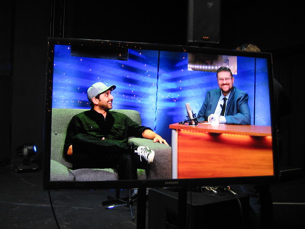 A video screen off to one side shows what actually appears on television. Here Jesse Egan is having a laugh with musician Mike Pinto.