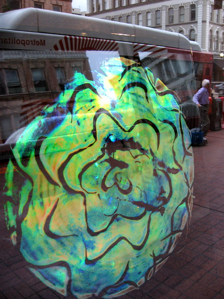 Unique holographic artwork painted on glass as seen through a Gaslamp window. Reflections of life on the street are also visible.