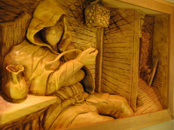 Amazing wood art. A hooded figure takes a break at an inn. Just Off The Road, Basswood, Randy Stoner.