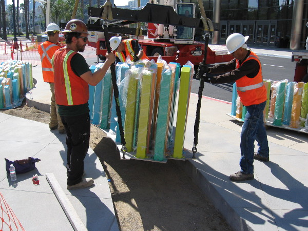 Construction workers carefully install new public art near the Marriott Marquis hotel's conference center. The colorful pylons are part of a sculptural creation titled Tide.