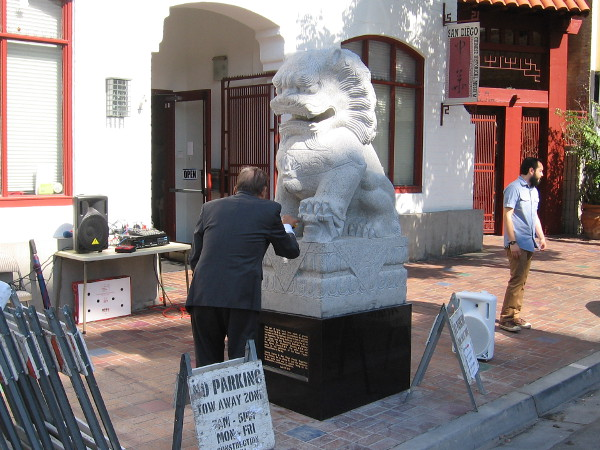 Founder of the San Diego Chinese Historical Museum, Dr. Alexander Chuang, prepares one of two stone lions for their unveiling ceremony.