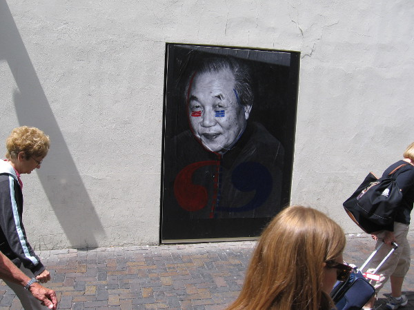 People walk through the breezeway between MCASD and the Santa Fe Depot. Three large portraits address the theme of political and domestic violence.