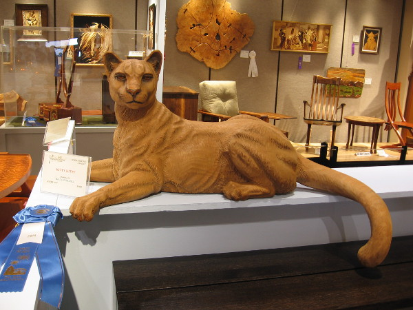 A mountain lion carved from wood keeps guard among other spectacular works of art. Kitty Kitty, Mahogany, Bill Churchill.