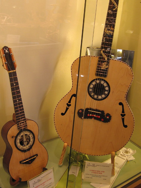 Two very cool handmade guitars with an Alice in Wonderland theme. I see clocks, the White Rabbit, a mad tea party, even a mustache!