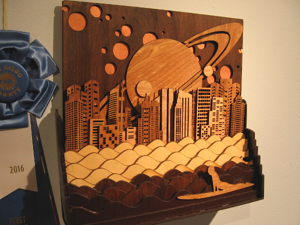 I love the cosmic layered wood sky with Saturn behind buildings. Night Surfing, Hardwood Plywood, Robert Stafford.