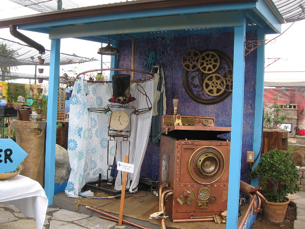 Some steampunk contraptions at the outdoor garden show. I see a cool steampunk washing machine and a weird metal Mad Hatter taking a shower.