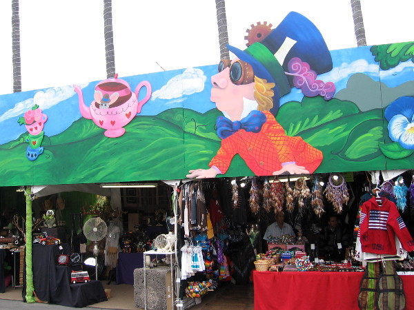 A long colorful mural above some fair vendors depicts beloved characters created by Lewis Carroll. Their appearance has evolved due to popular culture and now incorporate steampunk elements like goggles.