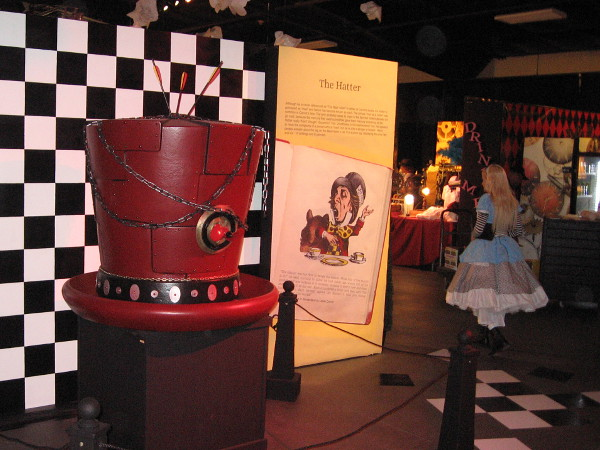 I've spotted Alice! She's passing a huge hat possibly worn by The Hatter.