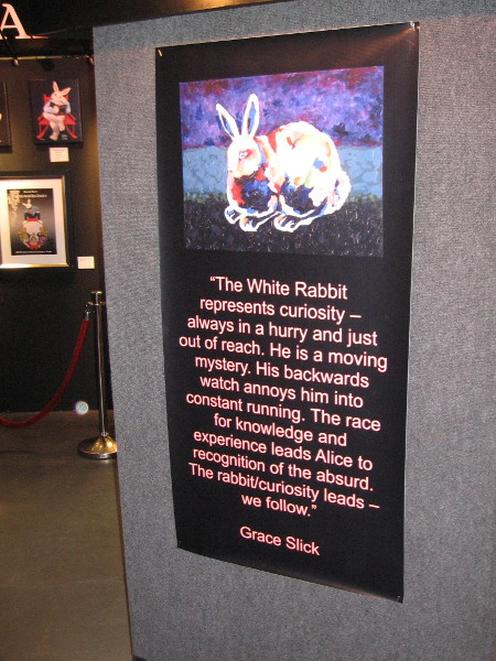 The White Rabbit represents curiosity--always in a hurry and just out of reach. He is a moving mystery.