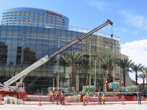 A big crane lifts sections of the artwork into position on a sunny Saturday morning in San Diego. The Marriott Marquis' brand new conference center shines in the background.