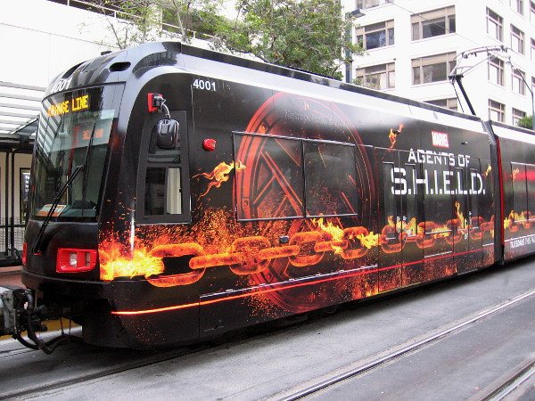 2016 San Diego Comic-Con will bring fans a new version of the familiar Agents of S.H.I.E.L.D. trolley wrap. This year, the design features a burning chain!