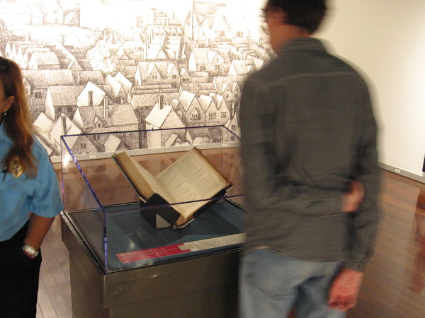 Visitor to art gallery at the downtown San Diego Library looks at a rare Shakespeare First Folio, open to Hamlet. The nearby wall features a mural of 17th century London and the original Globe Theatre.
