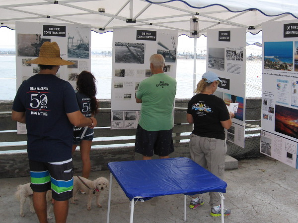 Visitors to the Ocean Beach Pier during its 50th anniversary celebration look at posters with information that concern the amazing concrete pier's construction and history.