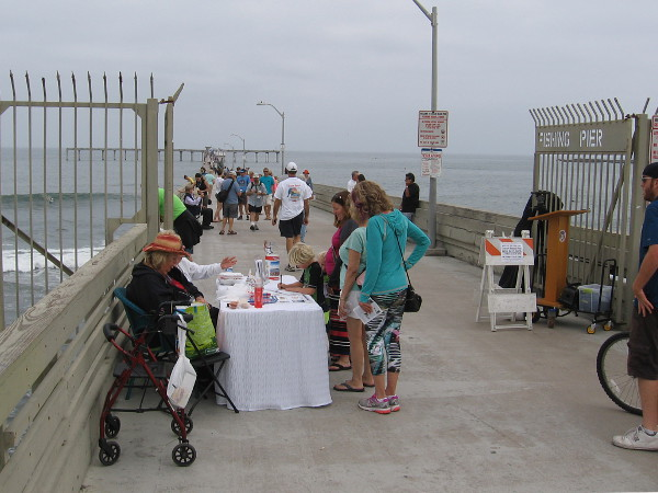 A table near the OB Pier gate welcomes people to the 50th anniversary celebration with flyers and event info.