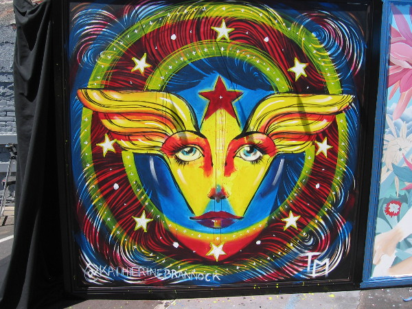 The left panel, depicting an abstract face of Wonder Woman, is being painted by San Diego artist Katherine Brannock.