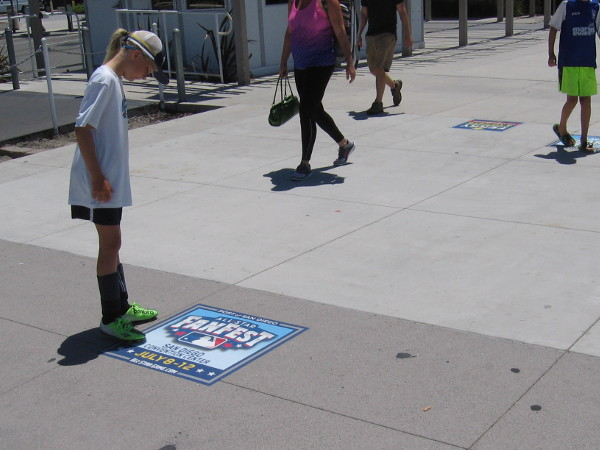 A young person checks out an All-Star Fanfest decal on the sidewalk behind the San Diego Convention Center. Promotional graphics have been placed in many popular walking spots.