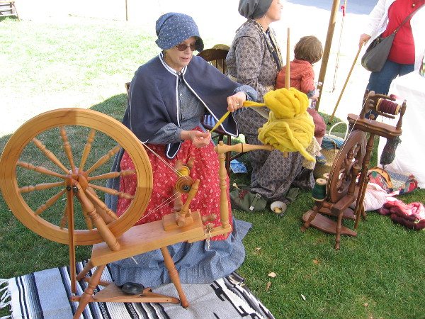 A lady in a bonnet at a spinning wheel was making wool yarn.