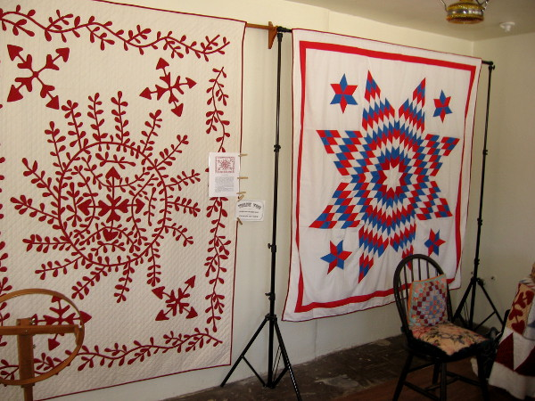 Two quilts on one wall greet visitors as they enter Threads of the Past. On the left is a modern version of the 1850s Juana Machado Quilt.