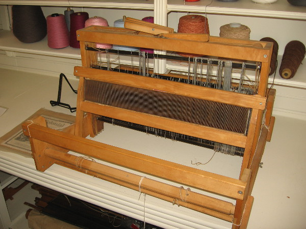 A wood Colonial Loom on display in Threads of the Past.