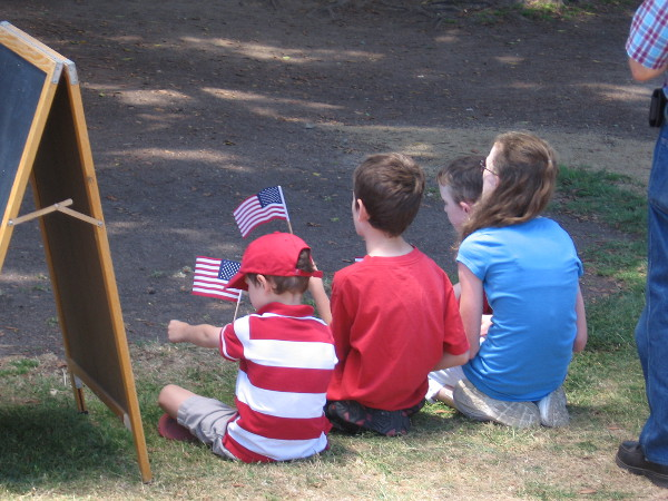 Kids listening to the speeches wave American flags.