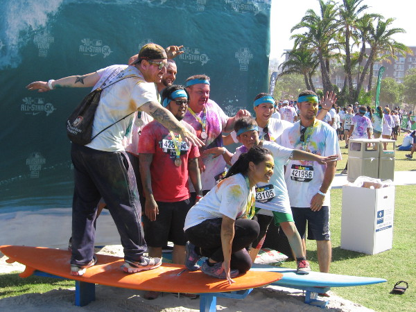 Friends posing for a photo on surfboards at Waterfront Park during the MLB All-Star 5K Color Run.