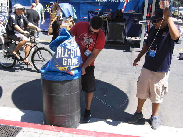 Here's something you don't see every day. A guy is putting an All-Star Game cover on a trashcan!